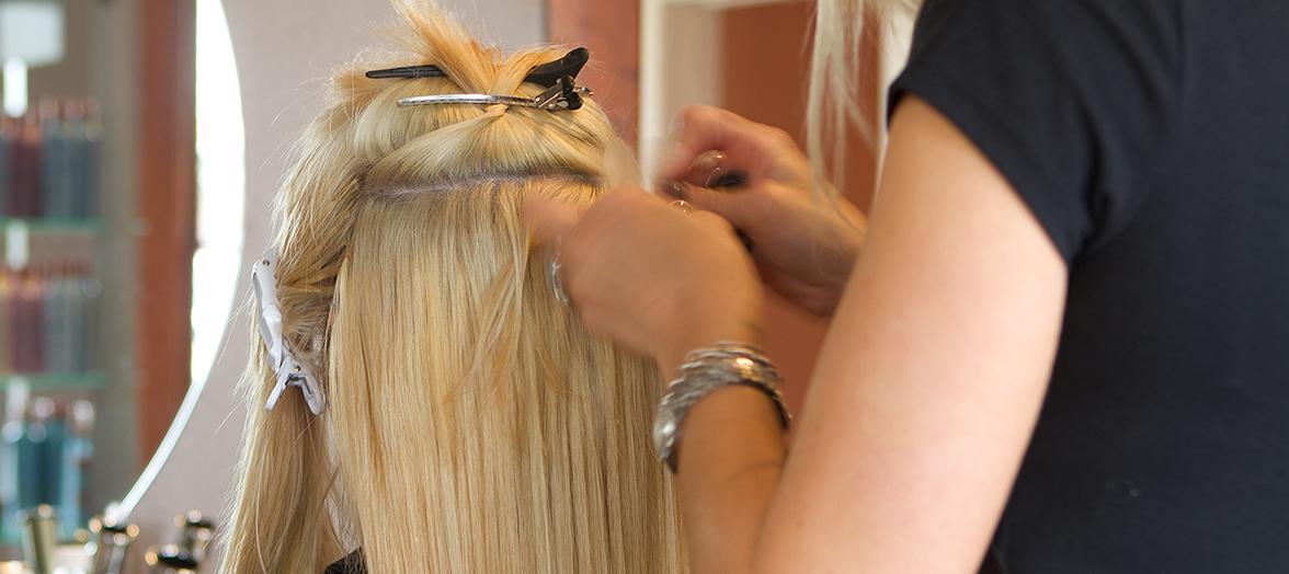 Das Foto zeigt, wie eine Friseurin gerade Clip In Extensions an den Haaren einer Kunding befestigt