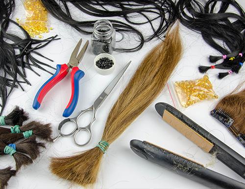 Das Foto zeigt viel Extensions Zubehör und Haarverlängerungen zusammen auf einem weißen Tisch