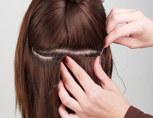 Das Foto zeigt eine Frisörin beim Einsetzen von Extensions zur Haarverdichtung einer Kundin