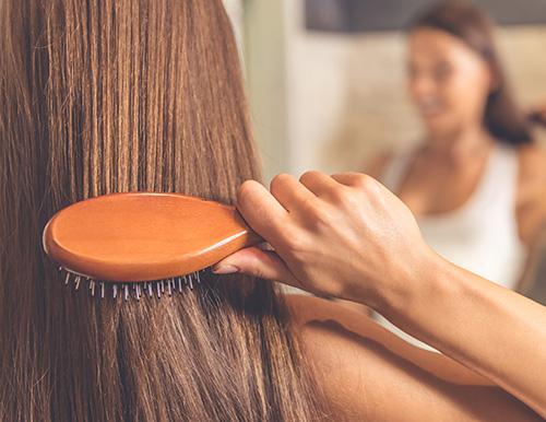 Das Foto zeigt eine Frau, wie sie sich gerade die glatten Haare bürstet