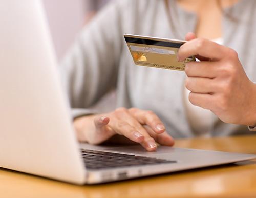 Das Foto zeigt eine Dame vor ihrem Laptop mit einer Kreditkarte in der Hand