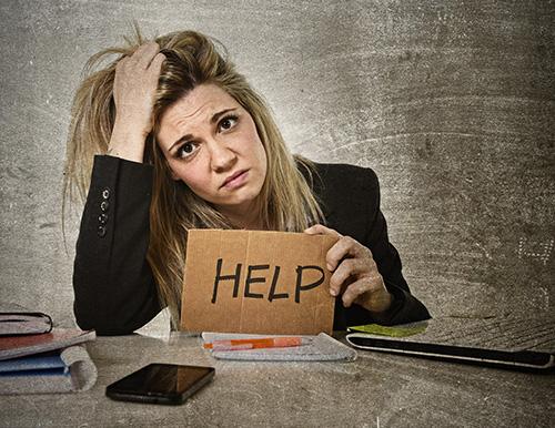 Das Foto zeigt, wie eine Frau mit schmerzverzerrtem Gesicht ein Schild mit der Aufschrift HELP in den Händen hält